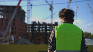 Back view of builder with black curly hair in green vest looking in side, putting on head the helmet on unfinished construction background.