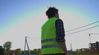 Back view of builder with black curly hair in green vest looking on construction process, putting on head the helmet on unfinished construction background.