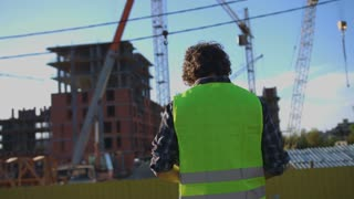 Back view of builder with black curly hair in green vest putting on head the headphones on unfinished construction background.