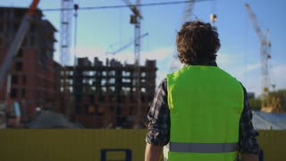 Back view of builder with black curly hair in green vest standing on unfinished construction background.