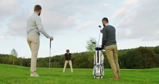 Background of handsome man playing golf on the pitch. His male friends with clubs watching on the first plan. Outside