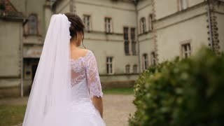 Backview of beautiful bride walking in white dress and spinning near the castle.