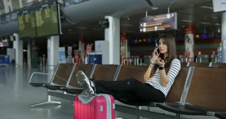 Beautiful attractive woman talking on smart phone with friend and putting here legs on the baggage while waiting for here flying in airport lounge.