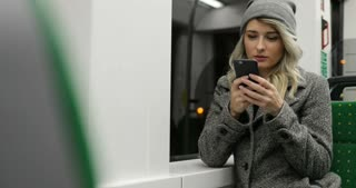 Beautiful blond girl on the phone dials the message in publick transport. Woman typing with two fingers.