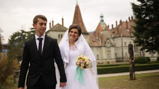 Beautiful Bride and Groom walking at the park near old antique castle