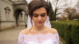 Beautiful bride walking in white dress and smiling near the old castle.