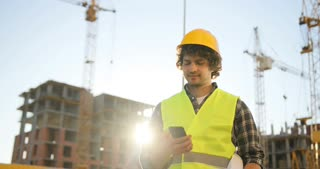 Beautiful builder with black curly hair in yellow helmet and green vest talking on cell phone with friend, smiling on unfinished construction background.