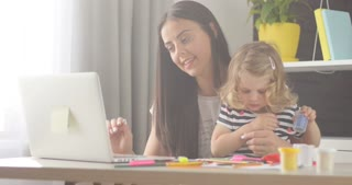 Beautiful caucasian woman with black long hair typing on laptop while her dauther opening box with plasticine on home background.