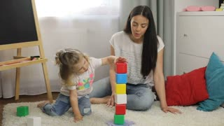 Beautiful little girl with blond curly hair and her mother with black long hair playing with cubes siting on the floor in room. Indoor.