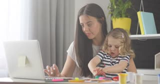 Beautiful little girl with blond curly hair opening box with plasticine while her mother working on laptop at home. Indoor.