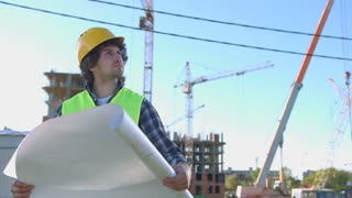Beautiful young builder in protected yellow helmet and green vest looking construction and analysing drawing on unfinished construction background.