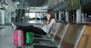 Beautiful young tourist girl with backpack and carry on luggage in international airport, waiting for her flight, looking upset. Talking on phone