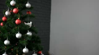 Beautiful young woman decorating the Christmas tree by red,silver toys on grey background.
