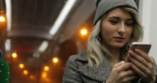 Blonde cute girl browsing on her phone while travelling on the public transport. Night city Lights