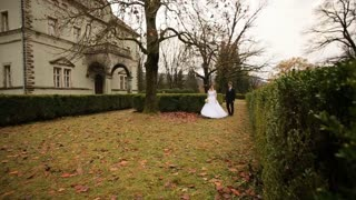 Bride and groom walking on the autmn leaves near the old castle.