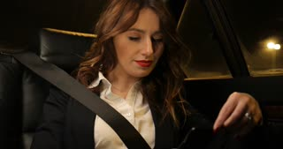 Business attractive woman rides on the backseat of car and working in her phone