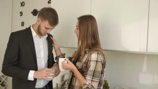 Business man and his wife drinking morning coffe before work and smiling at the kitchen