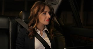 Business woman works at a laptop in the backseat of car