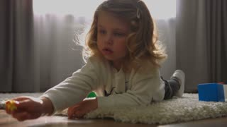 Carmind little girl with blond curly hair lying on the floor and playing the little toy on home background. Indoor.