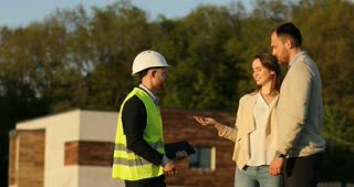 Caucasian architect in white helmet shaking hand of client. Builder and young couple standing near building, smiling. Outdoor.