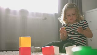 Caucasian beautiful little girl with blond curly hair playing with little toy siting on the floor in home. Indoor.