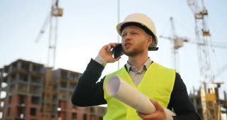 Caucasian builder in white helmet and yellow vest holding drawing and talking on mobile phone on unfinished construction background.