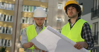 Caucasian builder in white helmet talking on cell phone while his colleague holding drawing on unfinished construction background. Close up.