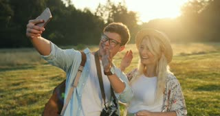 Caucasian cheerful young couple having a videochat on the smartphone device while standing in the field on the summer day.