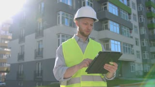 Caucasian handsome builder with white protected helmet and green safety vest using tablet for fixing the stage of construction on the background built house.