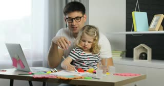 Caucasian little girl with blond curly hair using paints for drawing on a sheet of paper siting with her father in home.