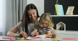 Caucasian woman with long black hair and her little dauther with blond curly hair driwing using paints, looking on camera and smiling with teeth. Indoor.