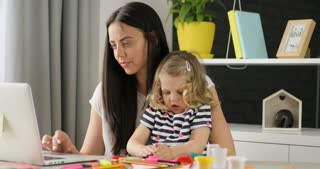 Caucasian young woman with black long hair using laptop for shopping while her dauther playing with plasticine on home background.
