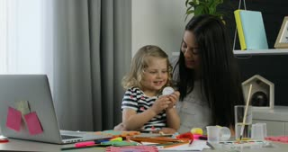 Charming caucasian little girl with blond curly hair and her mother with black long hair siting on the table in room. Indoor.