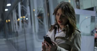 Charming woman is typing on a phone, outdoors in the city at night.