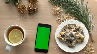 Christmas top view. Smartphone with green screen on wooden table. Christmas decoration, biscuits, tea. Chroma key