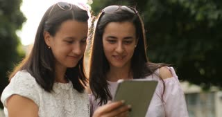 Close friends checking the tablet device outdoors.