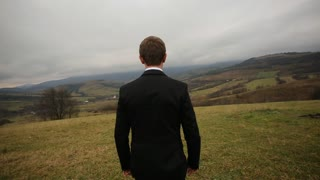 Close up back view of groom walking on the mountain hill