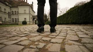 Close-up of mans feet walks on the stone pathway in the park near castle.