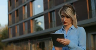 Close-up portrait of a beautiful business woman holding and using tablet outside, smiling looking at camera. Modern architecture building background