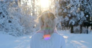 Close up portrait of attractive girl wearing a winter white pullover and pink scarf goes down the winter park, sun is shining, than turns to camera and smiles. Woman enjoying snowfall