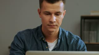 Close up portrait of confuse young business man in casual shirt working on the laptop in the stylish office.
