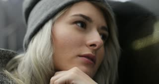 Close-up portrait of pretty depressed young blond girl in warm hat and jacket riding on public transport at night. She feel cold