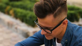 Close up portrait of young attractive man in the glasses looking to the camera and smiling on the city background. Side view.