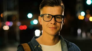 Close up portrait of young stylish man with glasses in the city centre at the evening time.