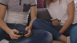 Close up shot of atracttive young couple relaxing at home, man playing video game, woman using smart phone.