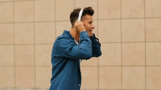 Close up shot of attractive happy man listening the music in headphone and dancing while walking near the airport.