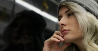 Close up shot of depressed, sad girl riding a public transport at night. She looking out the window and breathing heavily