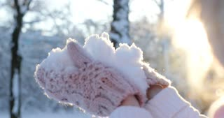 Close up shot of hand, young woman blowing snow, happy winter time in big city of charming girl having fun in park, enjoying snowfall,