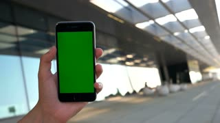 Close up shot of man hands holding the smart phone with green screen on airport background. Chroma key.