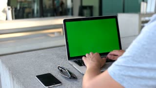 Close up shot of man hands using laptop with green screen while sitting in the airport. Chroma key.